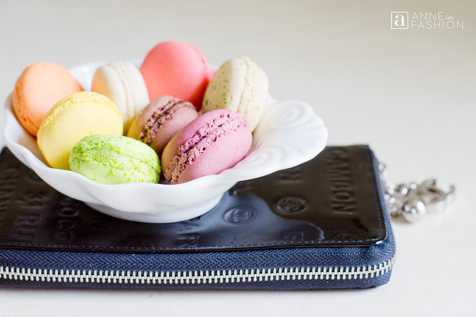 French macarons in dish with Chanel clutch wallet bag